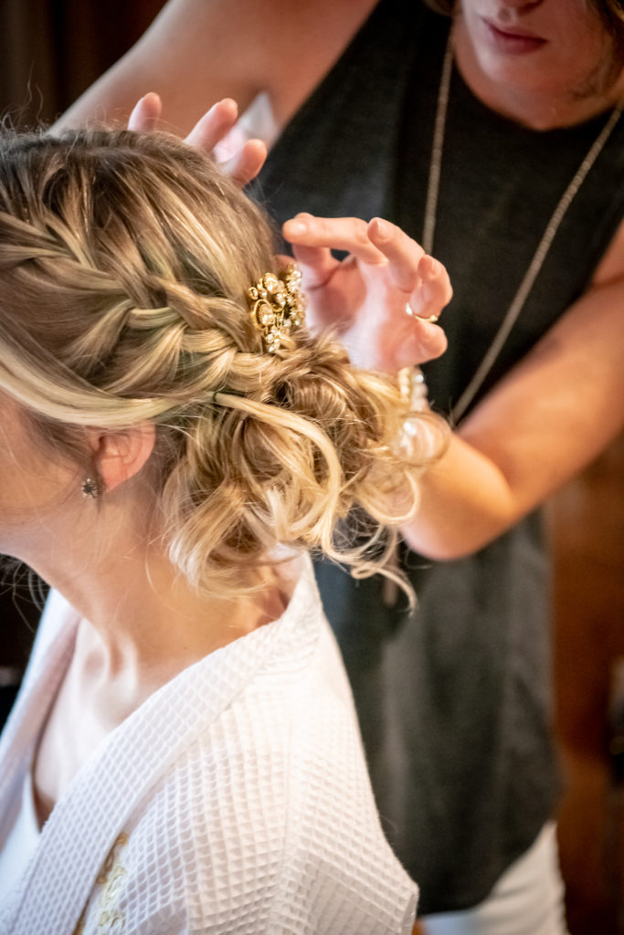 bride getting her hair done for her wedding